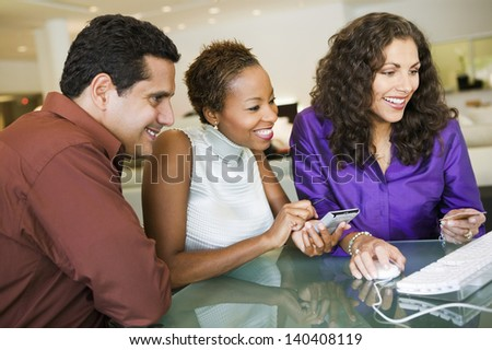 Happy multiethnic couple making purchase through computer in the furniture store
