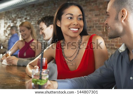 Happy multiethnic couples with cocktails sitting at the bar - stock photo