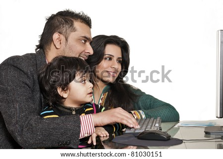 happy multiethnic family of three enjoying together, happy mother and father teaching their son on computer - stock photo