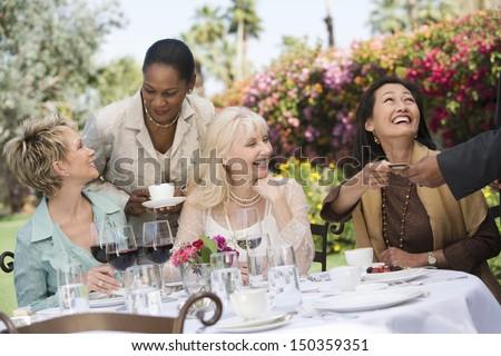 Happy multiethnic female friends enjoying dinner party in garden - stock photo
