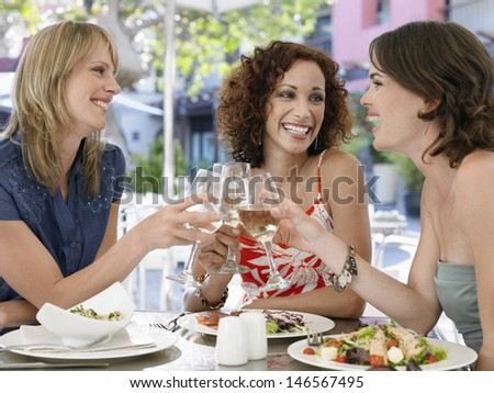 Happy multiethnic female friends toasting wine at outdoor cafe - stock photo