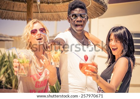 Happy multiethnic friends drinking cocktails - Afroamerican man and two caucasian girls toasting drinks at party - Young people partying in a club on the beach - stock photo