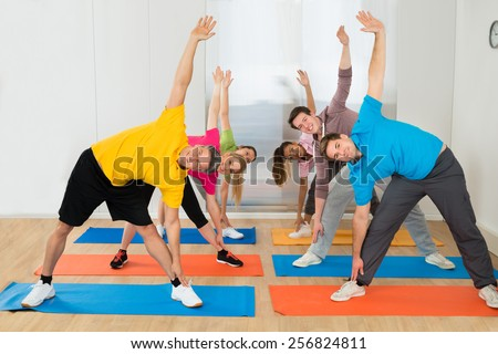 Happy Multiethnic Friends Exercising Together At Gym - stock photo