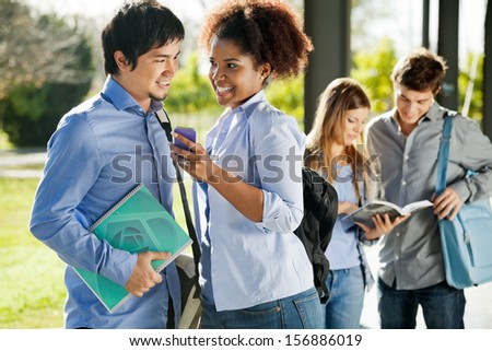 Happy multiethnic friends with mobilephone and book looking at each other in college campus - stock photo
