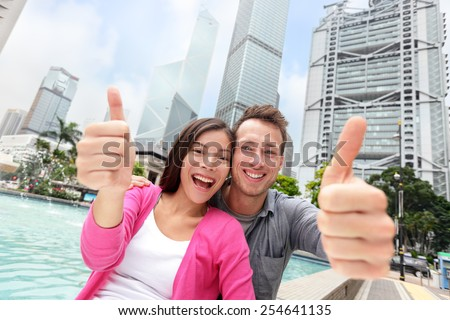 Happy multiethnic/ multicultural tourists couple showing thumbs up in satisfaction travelling in Hong Kong city, Asia. Young Asian and Caucasian adults smiling at camera - travel people - stock photo