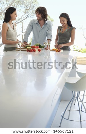 Happy multiethnic young friends communicating while preparing food at kitchen counter - stock photo