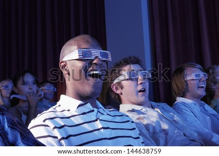 Happy multiethnic young men watching a 3-D movie in the theatre - stock photo