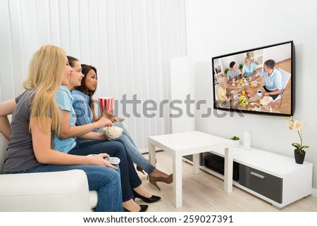 Happy Multiethnic Young Women Sitting On Couch Watching Movie - stock photo