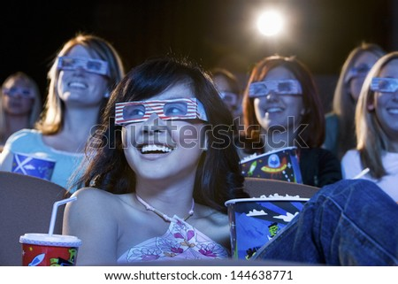 Happy multiethnic young women watching a 3-D movie in the theatre - stock photo