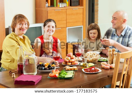 happy multigeneration family  together over celebratory table at home