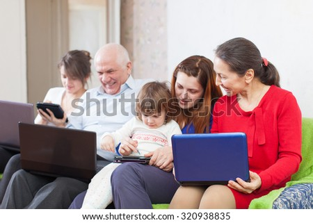 Happy multigeneration family uses few various portable computers in home interior