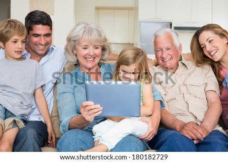 Happy multigeneration family using digital tablet at home - stock photo
