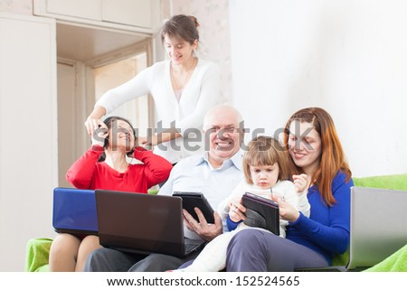 happy multigeneration family using few portable computers in home