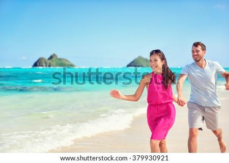 Happy multiracial Asian Caucasian couple having fun walking on perfect turquoise Lanikai Hawaii beach for summer vacation on Hawaiian island, Oahu, USA. - stock photo