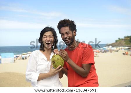 Happy multiracial couple enjoying vacation drinking coconut water on the boardwalk of Ipanema, Rio de Janeiro. - stock photo