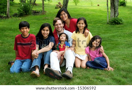 Happy multiracial family sitting on lawn - stock photo