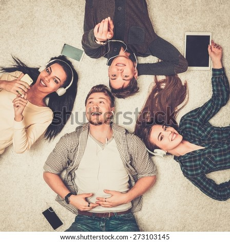 Happy multiracial friends relaxing on a carpet with gadgets  - stock photo