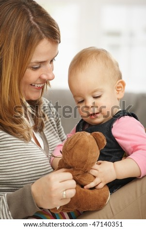 Happy mum and baby girl cuddling holding teddy bear. - stock photo