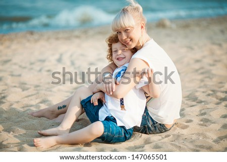 happy mum and her red head son having fun together outside on the beach