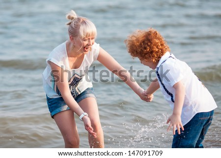 happy mum and her red head son having fun together outside on the beach, playing with water - stock photo
