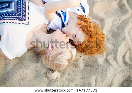 happy mum and her red head son laying on sand on the beach, close up - stock photo