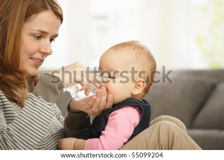 Happy mum holding baby girl in arms smiling baby drinking from feeding bottle.? - stock photo