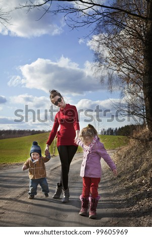 happy mum walking with her two children