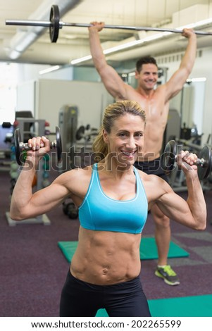 Happy muscular man and woman lifting weights at the gym - stock photo