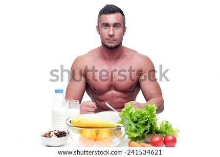 Happy muscular man sitting at the table with healthy food  - stock photo
