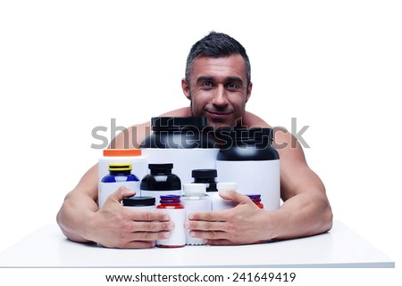 Happy muscular man sitting at the table with sports nutrition