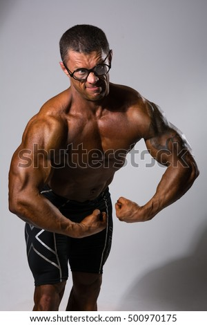 Happy muscular man with a naked torso and funny glasses. Bodybuilder demostriruet their muscles on a gray background