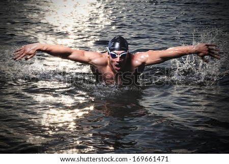 Happy muscular swimmer wearing glasses and cap at swimming pool and represent health and fit concept .  - stock photo