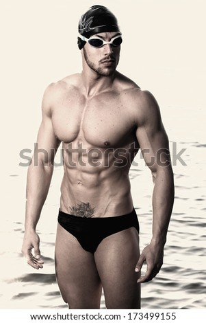Happy muscular swimmer wearing glasses and cap at swimming pool and represent health and fit concept . Fashion colors. - stock photo