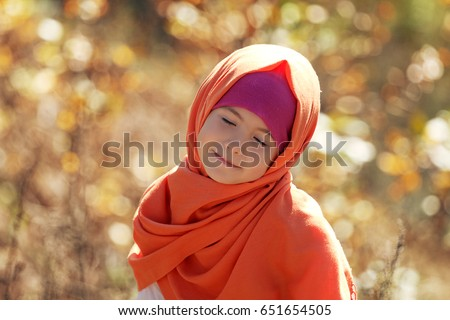 Happy Muslim child smiling with closed eyes