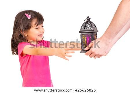 Happy Muslim family in Ramadan - Cute little girl feeling happy when her dad giving her Ramadan lantern (Fanos) - stock photo