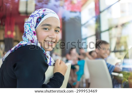Happy Muslim family in restaurant - stock photo