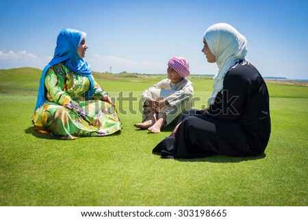 Happy Muslim family on green meadow - stock photo