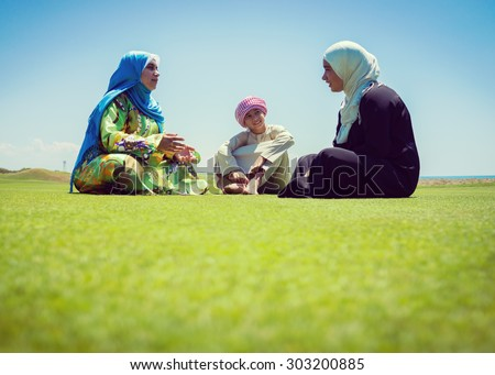 Happy Muslim family on green meadow