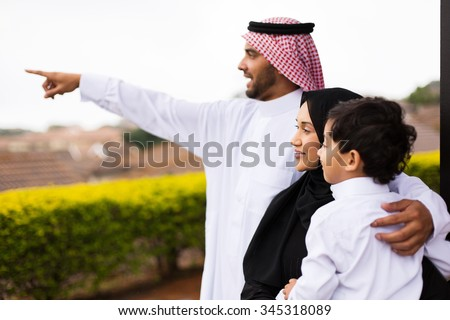 happy muslim family outside their home pointing - stock photo