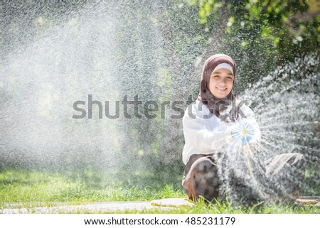 Happy muslim girl on summer meadow splashing water having fun and happy time