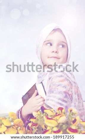 Happy muslim little girl holding Koran - stock photo