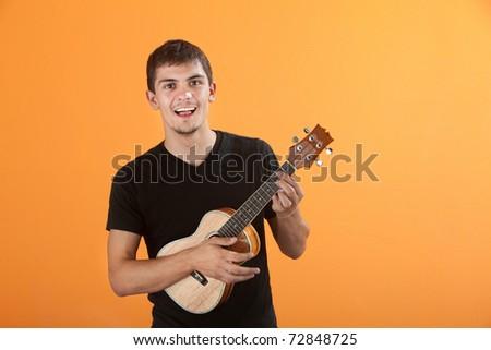 Happy Native American teen playing a ukulel - stock photo