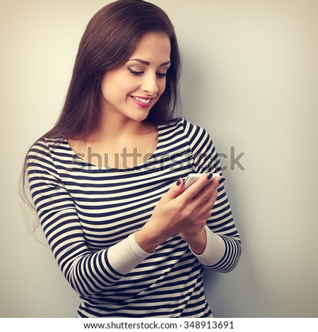 Happy natural emotion woman texting the sms on mobile phone. Vintage portrait