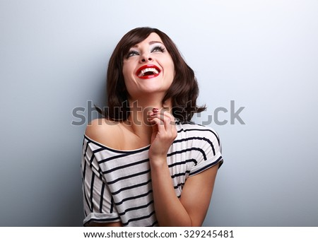 Happy natural toothy laughing young woman looking up on blue background with empty copy space