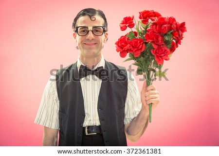 Happy nerd man with glasses and red roses flower bunch on pink for valentine day - stock photo