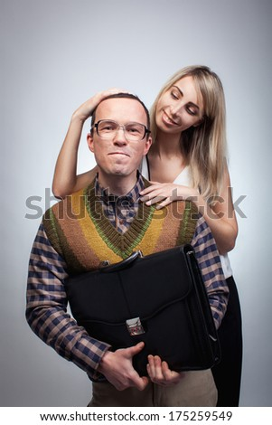 Happy nerd with his beautiful girl, studio shoot - stock photo