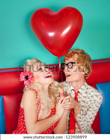 Happy nerdy couple celebrating valentine's day - stock photo