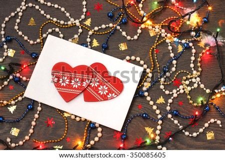 Happy New year and Merry Christmas!  New Year's congratulation, red decorative jewelry in the form of heart on an envelope, a color beads, confetti and garland on a wooden table. Card, invitation. - stock photo