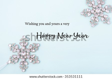 Happy New Year Background with snowflake ornaments on pale blue wood with sample text greeting.