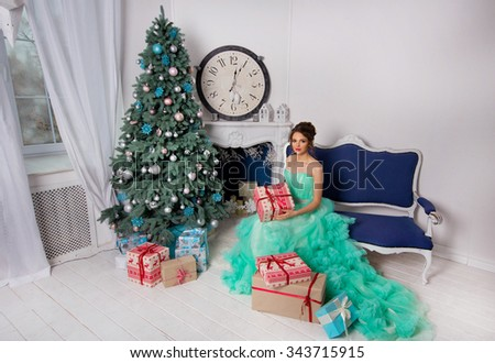 Happy new year! Beautiful cheerful girl in gorgeous evening dress over Christmas backgraung. Christmas tree and presents. - stock photo